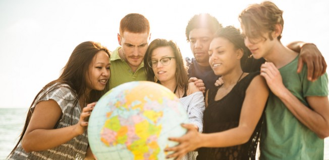 Diverse Group of Students Gathering round a Globe