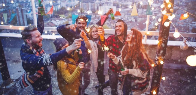 group of people with sparklers on rooftop terrace