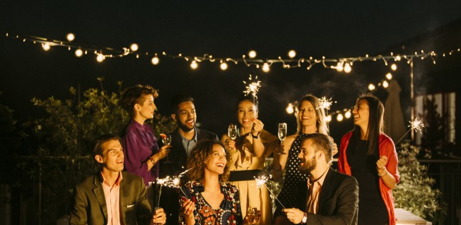 Group of People at Party Lighting Sparklers in the Dark