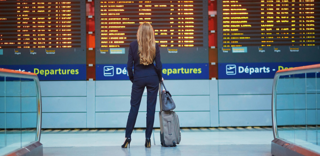 young businesswoman standing in front of departure screen at airport