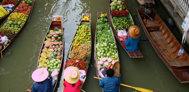 Vendors at the floating markets paddle along the banks to sell their goods.